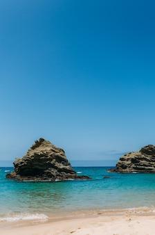 Colpo verticale di un oceano con due grandi rocce vicino alla riva sabbiosa e cielo blu chiaro