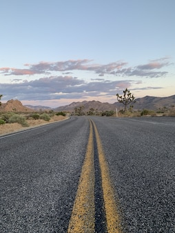 Ripresa verticale di una strada attraverso colline e montagne durante il tramonto