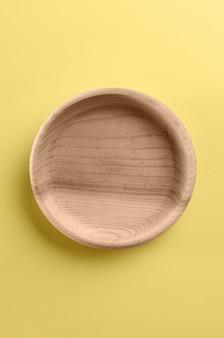 Colpo verticale del vassoio in legno rotondo su sfondo giallo con spazio di copia