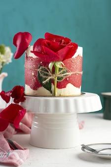 Ripresa verticale di una piccola torta fantasia con una rosa rossa su un vassoio bianco