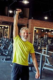 Ripresa verticale di un uomo caucasico maturo sorridente in abbigliamento sportivo che si esercita con manubri in palestra