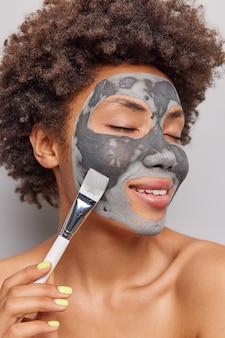 La foto verticale di una tenera donna afroamericana con capelli ricci naturali applica una maschera facciale di argilla