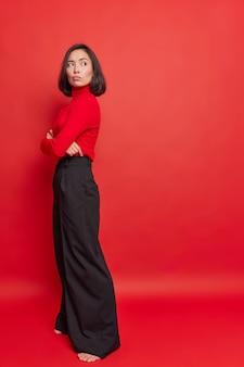 Colpo verticale di premurosa donna asiatica dispiaciuta con i capelli scuri tiene le braccia incrociate si gira dall'altra parte essendo insoddisfatta di qualcosa che indossa dolcevita e pantaloni neri si erge contro il muro rosso