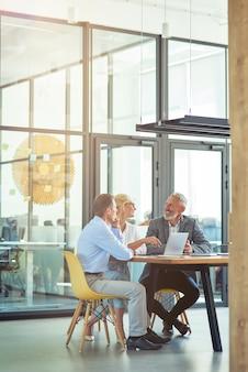 Ripresa verticale di tre colleghi maturi seduti nell'ufficio moderno o nello spazio di coworking usando
