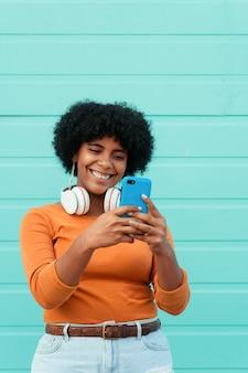 Ripresa verticale di una giovane donna attraente che indossa le cuffie usando il suo telefono