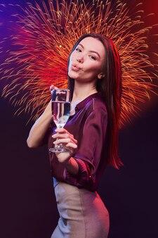 Colpo verticale di una giovane bella donna asiatica con un bicchiere di champagne che invia un bacio d'aria