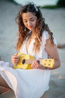 Ripresa verticale di una giovane donna con un bel vestito e una chitarra in spiaggia