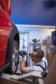 Ritratto verticale di vista laterale del meccanico di automobile maturo che cambia i pneumatici sull'auto rossa nell'officina di riparazione auto, spazio della copia