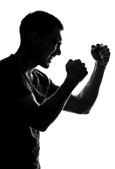 Sagoma verticale di un uomo aggressivo di profilo con sorriso, pugni piegati davanti a lui, posizione di combattimento