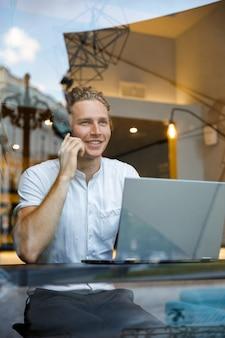 Verticale sorridente uomo d'affari ricci parlando da smartphone e distogliere lo sguardo mentre era seduto al tavolo con il computer portatile nella caffetteria