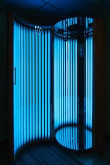 Solarium verticale con lampade ultraviolette a luce blu incandescente