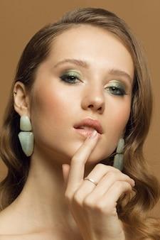 Foto di bellezza studio verticale di una giovane ragazza con pelle pulita, trucco alla moda e acconciatura.