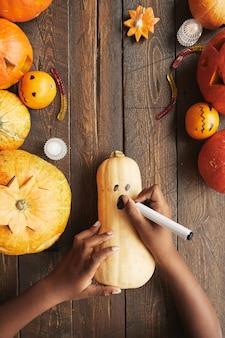 Colpo verticale dall'alto verso il basso di una persona irriconoscibile che disegna una faccia spaventosa sulla zucca con un pennarello posteriore per halloween