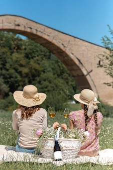 Donne irriconoscibili verticali sedute con cappello di paglia che guardano la scena che tiene in mano la scena rurale del vino wine