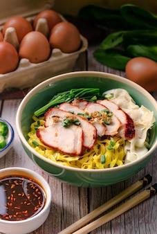 Ciotola di vista verticale di pasta all'uovo con carne di maiale arrosto che serve con salsa dolce e decorare con ingredienti da cucina come uova e cavolo cinese