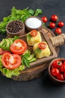 Vista verticale di verdure fresche tritate formaggio sul tagliere e spezie fascio verde sulla superficie nera