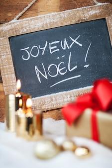 Vista verticale di regali di natale con candele e ardesia.