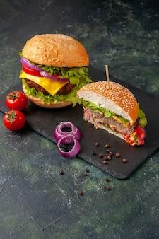 Vista verticale di interi gustosi panini tagliati e pomodori con cipolle di gambo sul vassoio nero sulla superficie scura