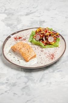 Vista verticale di farina di pesce e deliziosa insalata su un piatto sulla superficie bianca macchiata