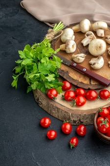 Vista verticale dei funghi crudi freschi e dei pomodori verdi del coltello del fascio sull'asciugamano del bordo di legno su fondo nero