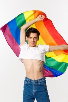 Vista verticale della persona queer felice in top corto e jeans che sventolano bandiera arcobaleno sollevata, celebrando la festa lgbtq, in piedi sopra il bianco.