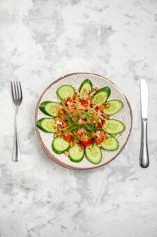 Vista verticale di fatti in casa sana deliziosa insalata vegana decorata con cetrioli tritati in una ciotola posate impostato su macchiato di superficie bianca