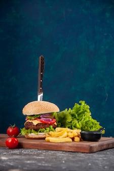 Vista verticale del coltello in sandwich di carne e patatine fritte pomodori con gambo sul ketchup di tavola di legno sulla superficie blu scuro