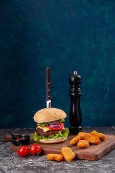 Vista verticale del coltello in gustoso panino di carne e pepite di pollo pomodori con gambo su ketchup di salsa di bordo di legno sulla superficie blu scuro