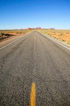 Vista verticale della lunga strada americana alla monument valley, stati uniti d'america