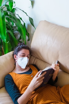 Vista verticale della maschera da portare d'uso della donna malata che legge un libro a casa. malattia da virus pandemico covida 19. concetto di salute.