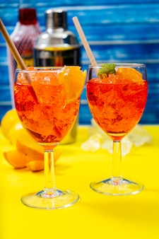 Vista verticale di due bicchieri del rinfrescante cocktail aperol spritz con menta