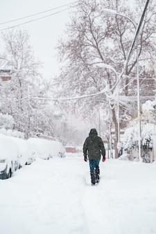 Vista verticale del viaggiatore irriconoscibile che cammina in mezzo alla neve.