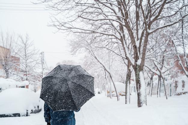 Vista verticale del viaggiatore irriconoscibile con un ombrello in mezzo alla neve.