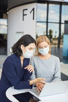 Mezzo busto verticale ritratto di due imprenditrici di successo che indossano maschere mentre si guarda lo schermo del laptop in piedi alla scrivania in edificio per uffici