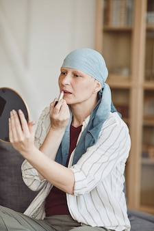 Ritratto verticale dai toni caldi della donna calva sicura di sé che si mette il trucco e il rossetto mentre si guarda nello specchio a casa, abbracciando la bellezza, l'alopecia e la consapevolezza del cancro