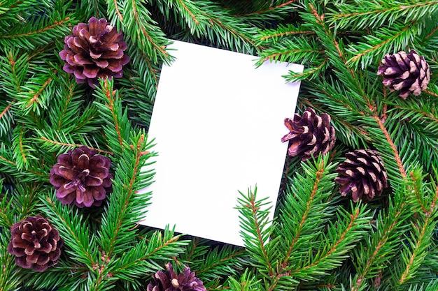 Carta bianca verticale e cornice composta da rami di abete e pigne. il foglio bianco si trova su uno sfondo