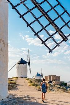 Verticale di giovane donna con una borsa a piedi tra vecchi mulini a vento e un castello a toledo, spagna.