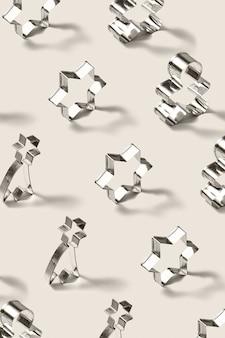 Modello di formine per biscotti in acciaio inossidabile verticale per biscotti fatti in casa a forma di stelle e pan di zenzero natalizio, su uno sfondo grigio chiaro con ombre morbide.