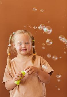 Verticalw aist up ritratto di ragazza carina con sindrome di down a soffiare bolle mentre posa contro la superficie marrone in studio