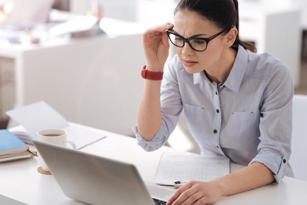 Operaio femminile molto attento rughe sulla fronte che tocca gli occhiali mentre guarda lo schermo del suo computer portatile