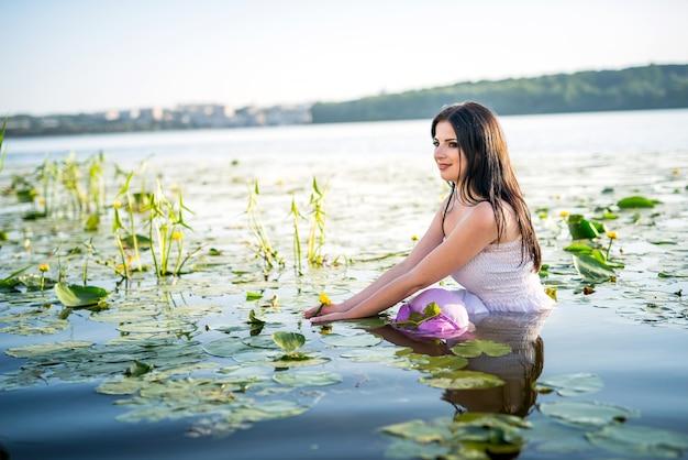 Donna molto attraente che si siede nell'acqua del lago