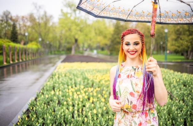 Una bellissima ragazza dalla pelle chiara con un trucco espressivo con lunghe trecce multicolori e un vestito floreale leggero. fai una passeggiata nel parco primaverile in tempo piovoso nuvoloso grigio con un ombrello bianco.