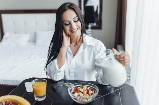 Molto bella ragazza bruna felice al mattino nella sua stanza al tavolo alla finestra