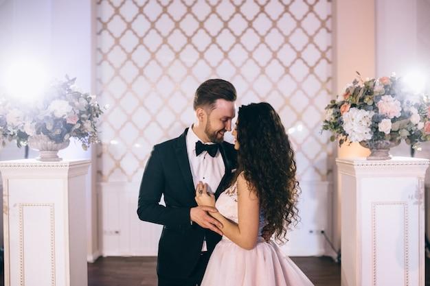 Sposi molto belli e felici stanno vicino a un arco di nozze splendidamente decorato durante la loro cerimonia di matrimonio