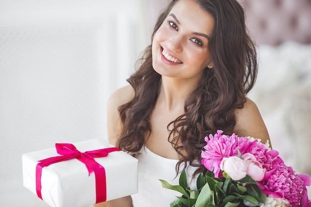 Donna molto bella con peonia e confezione regalo al chiuso