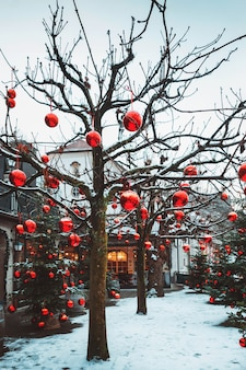 Alberi di natale molto ben decorati in un numero enorme di grandi palline rosse luminose, salisburgo, austria.