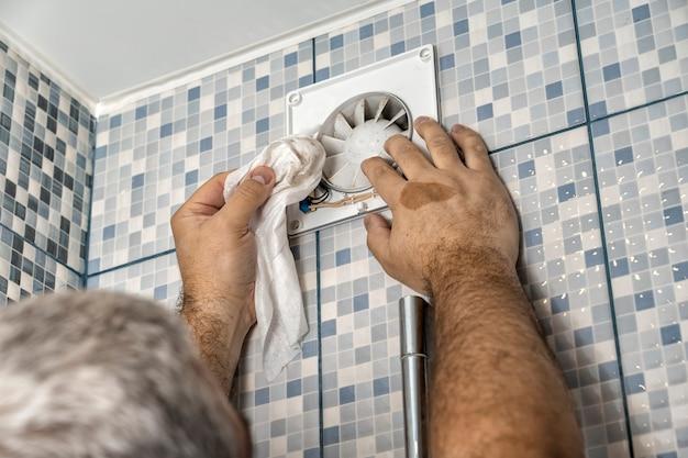 Uscita dell'aria molto sporca nel bagno. il professionista pulisce la griglia