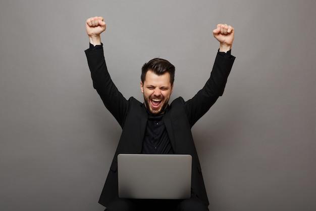Un uomo elegante molto eccitato in abito con cravatta valeva un laptop su uno sfondo grigio