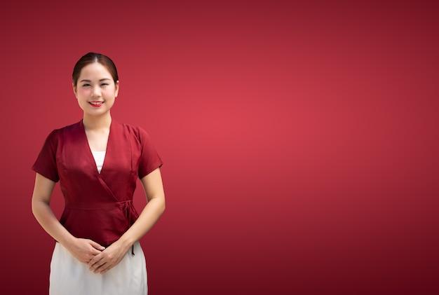 Presentazione felice sorridente della bella ragazza asiatica molto fresca ed energica su una priorità bassa rossa.