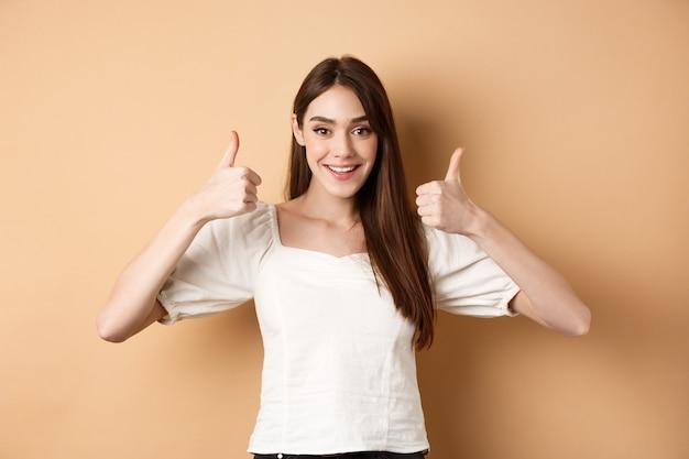 Molto bene. giovane donna felice e soddisfatta che mostra il pollice in su, sorridente positivo, approva e ama la scelta eccellente, ti elogia, fa un gesto ben fatto, sfondo beige.